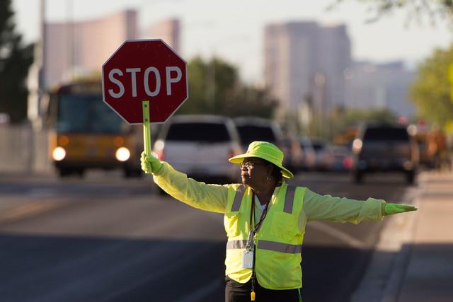 Crossing guard Patricia Bass assists children in crossing Tonopah Drive at Lake Mead Boulevard before classes at West Preparatory Academy in Las Vegas, Thursday, Oct. 6, 2016. (Jason Ogulnik/Las V ...