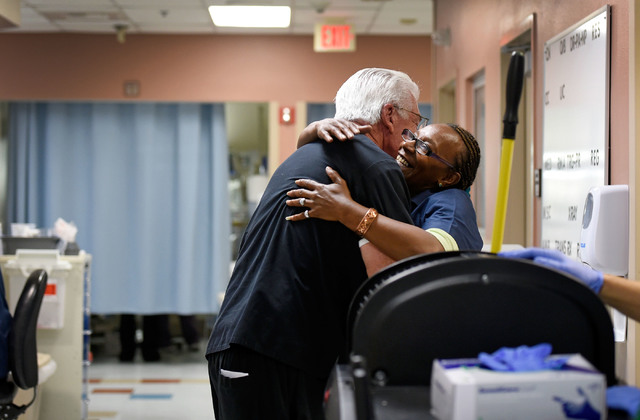 University Medical Center Chief of Staff Dr. Dale Carrison, left, greets environmental services worker Theresa McGowan as he begins his morning rounds in the emergency department at at the hospita ...
