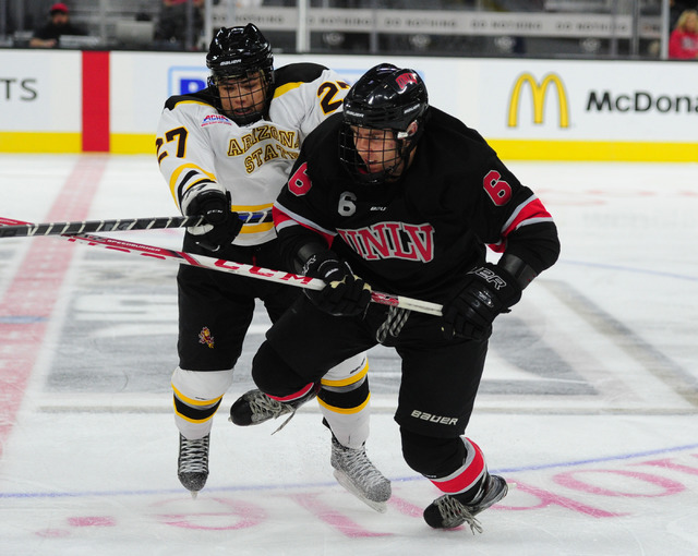 Arizona State forward Jon de Werd cross-checks UNLV defenseman Connor Hetzel during their ACHA Division II club hockey game at T-Mobile Arena  in Las Vegas Sunday, Oct. 9, 2016. UNLV won 3-2. (Jos ...