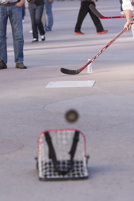A man hits a puck into a net during the Vegas Hockey Fan Fest at Toshiba Plaza in Las Vegas, Saturday, Oct. 8, 2016. Jason Ogulnik/Las Vegas Review-Journal