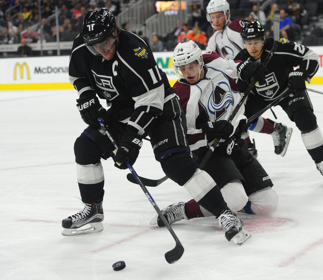 Los Angeles Kings center Anze Kopitar (11) and Colorado Avalanche center Carl Soderberg (34) battle for the puck in the first period of their NHL preseason hockey game at T-Mobile Arena in Las Veg ...