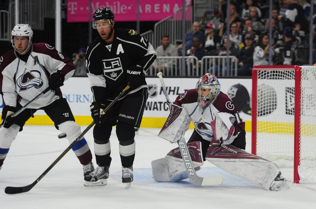 Colorado Avalanche goalie Semyon Varlamov makes a glove save in front of Los Angeles Kings forward Jeff Carter (77) and defenseman Erik Johnson (6) in the first period of their NHL preseason hocke ...