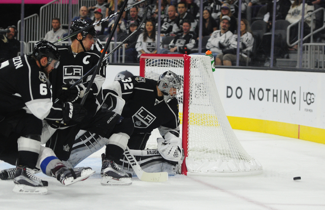 Los Angeles Kings goalie Jonathan Quick (32), defenseman Jake Muzzin (6) and center Anze Kopitar (11) watch the puck bounce off the boards in the second period of their NHL preseason hockey game a ...