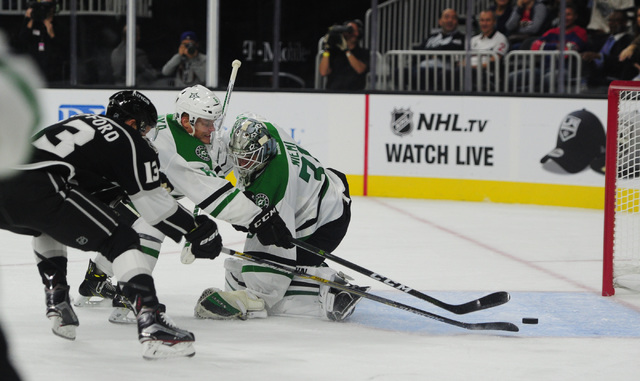 Dallas Stars defenseman Julius Honka, middle, clears the puck out of the crease while Los Angeles Kings left wing Kyle Clifford (13) attempts to score on goalie Antti Niemi (31) in the third perio ...