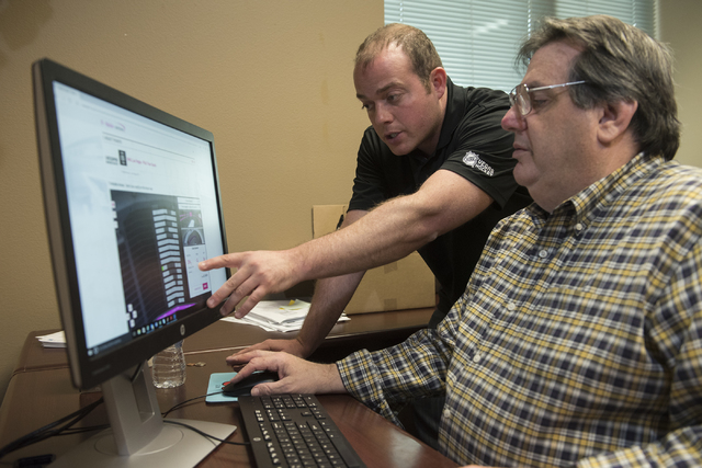 Todd Pollock, left, Vice President of Ticketing and Suites for the new Las Vegas hockey team shows Review-Journal reporter Steve Carp the process of purchasing season tickets from their NHL office ...