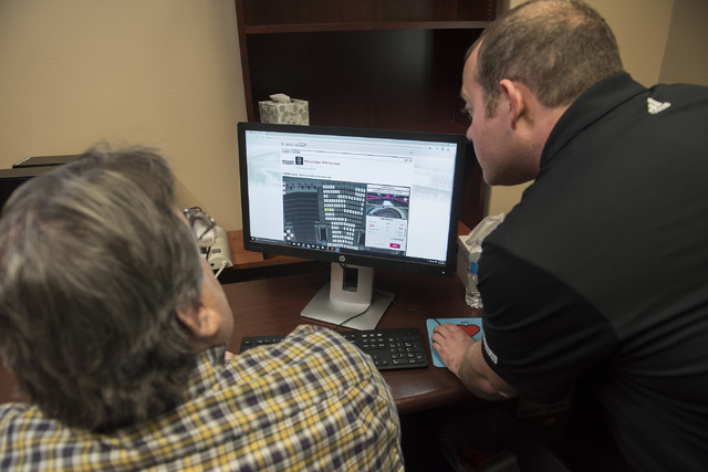 Todd Pollock, right, Vice President of Ticketing and Suites for the new Las Vegas hockey team shows Review-Journal reporter Steve Carp the process of purchasing season tickets from their NHL offic ...