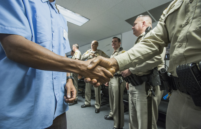 A former inmate shakes hands with Las Vegs police officers during a pre-vocational leadership workshop at Hope for Prisoners, 3430 E. Flamingo Road, on Thursday Aug. 18, 2016. (Jeff Scheid/Las Veg ...
