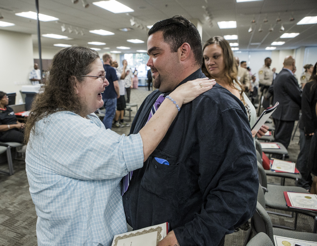 Adrian Romero is embraced by his mother after a Hope for Prisoners graduation at Metropolitan Police Department headquarters, 400 S. Martin Luther King Blvd., on Friday, Aug. 19, 2016. (Jeff Schei ...