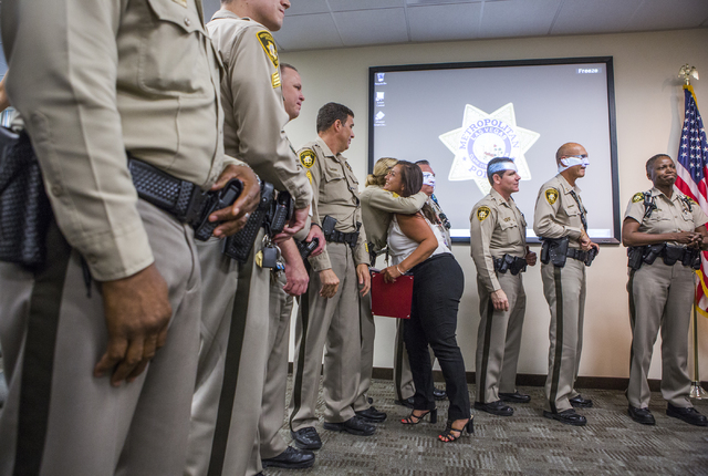 Angelica Kimber hugs a Las Vegas police officer after a Hope for Prisoners graduation at Metropolitan Police Department headquarters, 400 S. Martin Luther King Blvd., on Friday, Aug. 19, 2016. (Je ...