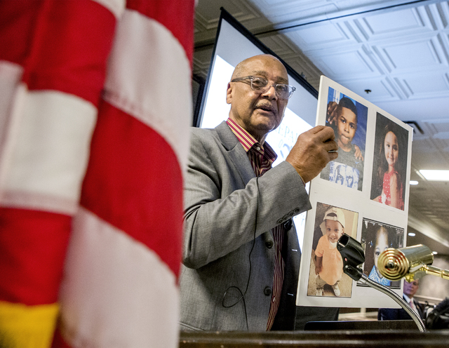 Bob Woodson, founder of the Center for Neighborhood Enterprise in Washington, D.C., holds photos of children who were murdered during the Repairing the Breach summit at Palace Station in Las Vegas ...