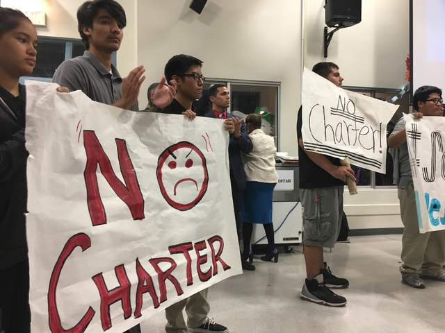 Students hold signs during a rally in the cafeteria at West Preparatory Institute for Academic Excellence in Las Vegas on Tuesday, Oct. 18, 2016, to protest the possibility of a charter-school tak ...