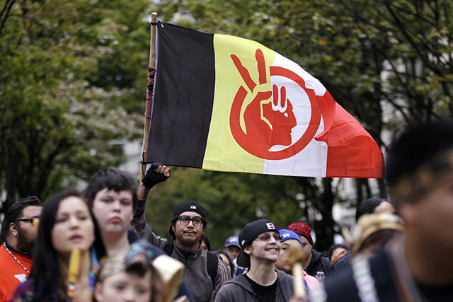 An American Indian Movement flag is flown during a march for Indigenous Peoples Day, Monday, Oct. 12, 2015, in Seattle. (Elaine Thompson/AP)