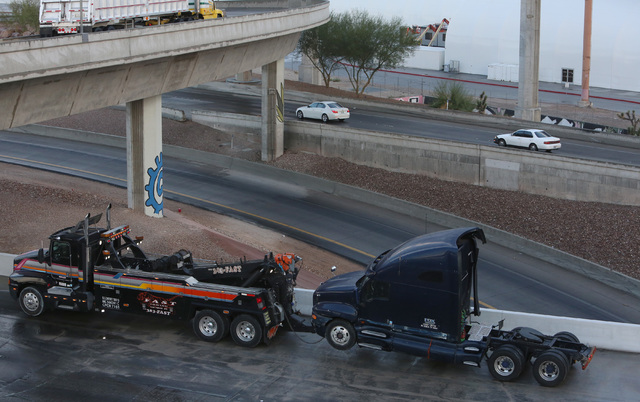 A jackknifed semitrailer is being removed by a tow truck on northbound Interstate 15 in the Spaghetti Bowl Monday, Oct. 24, 2016. Traffic is being diverted to northbound and southbound U.S. Highwa ...