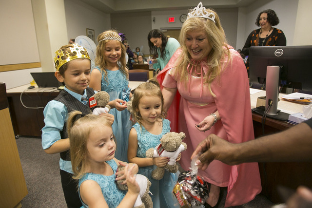District Court Family Judge Cynthia Giuliani and a courtroom bailiff hand out goodie bags and gifts to Chase, 6, Nevaeh, 3, Jessie, 9, and Leslie, 4, after finalizing the adoption process with the ...