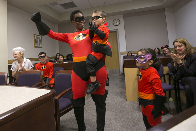 Cassandra Jones, 47, raises her hand in joy as she is joined by her new adopted family members, Xion, 2, Xenia, 5, second right, and Xander, 12, second left, after being sworn in by District Court ...