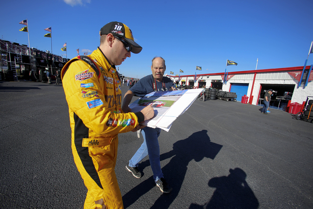 Kyle Busch signs an autograph for a fan as he walks back to the garage area during practice for Sunday's NASCAR Sprint Cup auto race at Talladega Superspeedway, Friday, Oct. 21, 2016, in Talladega ...