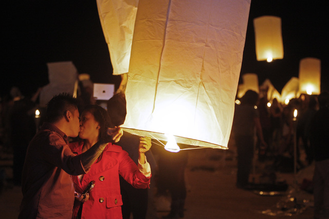 Junnie and Jade Ranole, from Las Vegas, kiss as they inflate a paper lantern at the RiSE Festival Saturday, Oct. 18, 2014 on a dry lake bed near Jean.  (Sam Morris/Las Vegas Review-Journal)