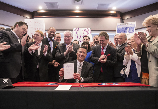 Nevada Gov. Brian Sandoval celebrates after signing Senate Bill 1 at the Richard TAM Alumni Center at UNLV on Monday, Oct. 17, 2016, in Las Vegas. The bill officially allows for a 65,000-seat dome ...