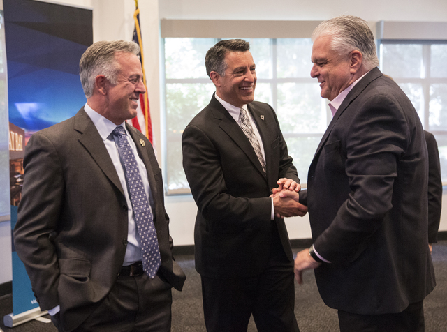 Sheriff Joe Lombardo, left, Gov. Brian Sandoval and Commissioner Steve Sisolak talk during a bill signing ceremony at the Richard TAM Alumni Center at UNLV on Monday, Oct. 17, 2016, in Las Vegas.  ...