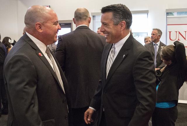 Nevada Gov. Brian Sandoval, right, talks with UNLV head football coach Tony Sanchez at the Richard TAM Alumni Center at UNLV on Monday, Oct. 17, 2016, in Las Vegas. (Benjamin Hager/Las Vegas Revie ...