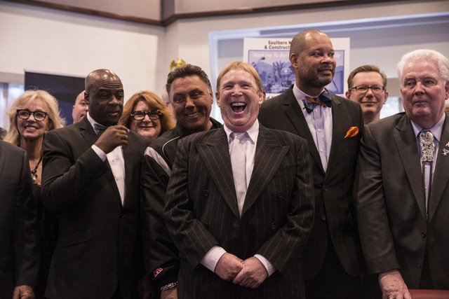 Oakland Raiders owner Mark Davis, middle, smiles moments before Nevada Gov. Brian Sandoval signs Senate Bill 1 at the Richard TAM Alumni Center at UNLV on Monday, Oct. 17, 2016, in Las Vegas. The  ...