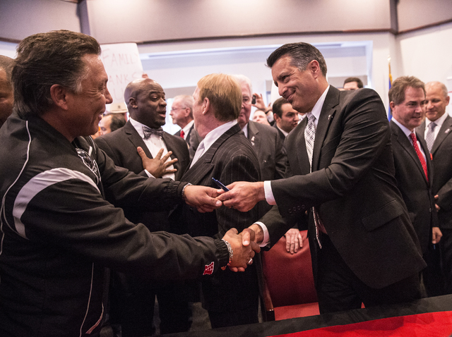 Nevada Gov. Brian Sandoval, right, celebrates with the crowd after signing Senate Bill 1 at the Richard TAM Alumni Center at UNLV on Monday, Oct. 17, 2016, in Las Vegas. The bill officially allows ...