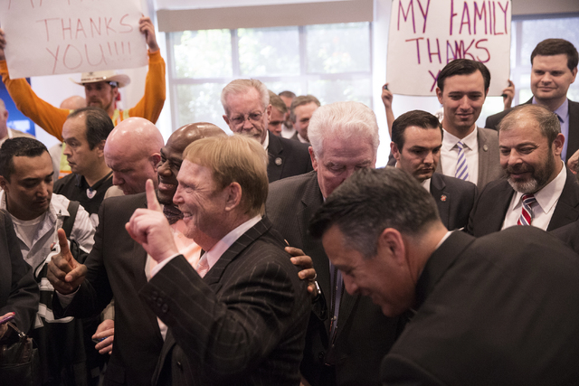 Oakland Raiders owner Mark Davis, left, celebrates with supporters moments after Gov. Brian Sandoval signed Senate Bill 1 at the Richard TAM Alumni Center at UNLV on Monday, Oct. 17, 2016, in Las  ...