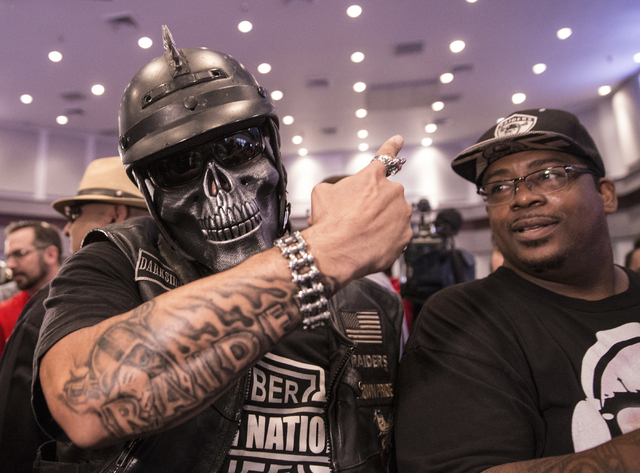 Raiders fan Eric Carrillo, left, celebrates moments after Nevada Gov. Brian Sandoval signed Senate Bill 1 at the Richard TAM Alumni Center at UNLV on Monday, Oct. 17, 2016, in Las Vegas. The bill  ...