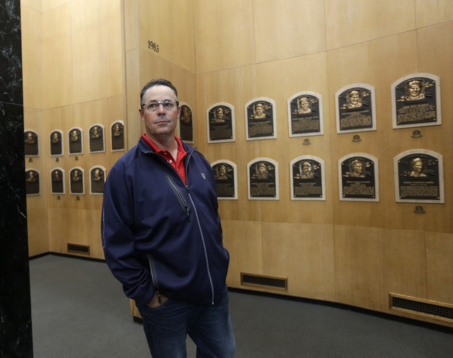 Former Atlanta Braves pitcher Greg Maddux walks through the Plaque Gallery during his orientation visit at the Baseball Hall of Fame on Monday, March 24, 2014, in Cooperstown, N.Y. (Mike Groll/AP)