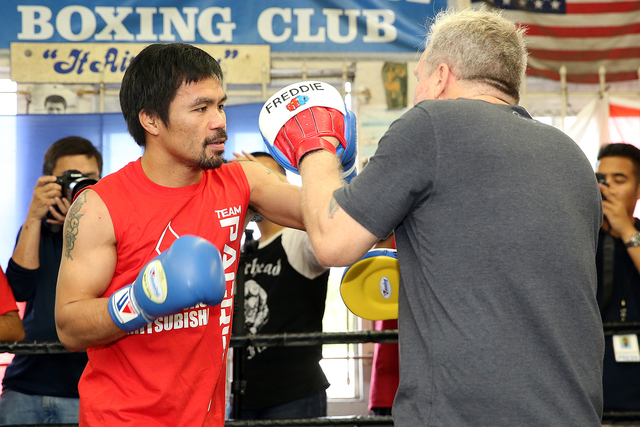 Manny Pacquiao (left) hits the mitts with trainer Freddie Roach at his Los Angeles media day last week. (Photo by Mikey Williams)