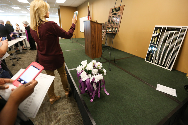People take photos of plaques with the names of domestic violence homicide victims during a remembrance ceremony at the Metropolitan Police headquarters in Las Vegas on Thursday, Oct. 6, 2016. (Br ...