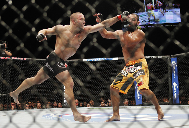 Georges St. Pierre, left, hits Johny Hendricks during UFC 167 at the MGM Grand Garden Arena in Las Vegas on Nov. 16, 2013. (Jason Bean /Las Vegas Review-Journal)
