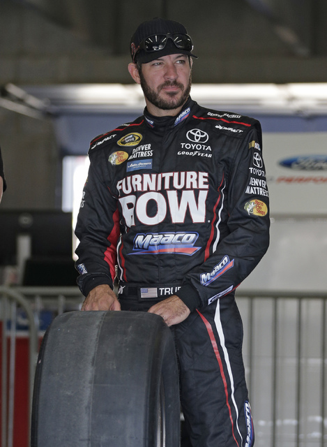 Martin Truex Jr. watches as his crew works on his car before practice for Saturday's NASCAR Sprint Cup series auto race at Charlotte Motor Speedway in Charlotte, N.C., Thursday, Oct. 6, 2016. (AP  ...