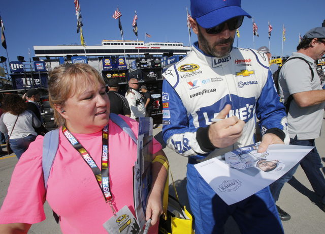 Sprint Cup Series driver Jimmie Johnson (48) signs autographs prior to practice for Sunday's Sprint Cup auto race at Martinsville Speedway in Martinsville, Va., Saturday, Oct. 29, 2016. (AP Photo/ ...