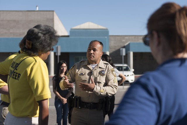 Las Vegas police Sgt. Jose Hernandez, center, speaks with volunteers during a canvassing event near Lake Mead Boulevard and Marion Street to find leads in the February homicide of Heriberto Diaz-M ...