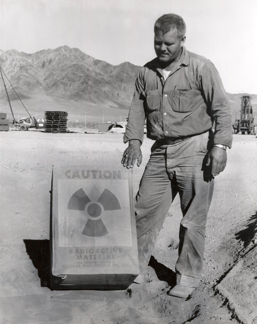 A worker stands by a radioactive materials sign in this undated photo at the former Nuclear Engineering Co. low-level nuclear waste landfill, 11 miles south of Beatty. (Las Vegas Review-Journal file)