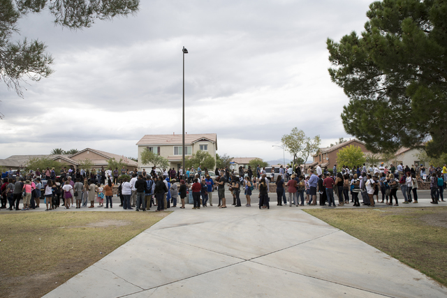 People line up outside of Cheyenne High School to attend a campaign rally for Democratic presidential nominee Hillary Clinton with President Barack Obama on Sunday, Oct. 23, 2016, in North Las Veg ...