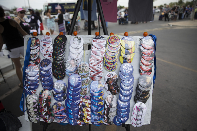 A vendor sells buttons outside of Cheyenne High School before a campaign rally for Democratic presidential nominee Hillary Clinton with President Barack Obama on Sunday, Oct. 23, 2016, in North La ...