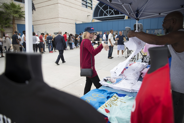 Jennifer Laporte of Petaluma, Calif., buys a shirt from a vendor outside of Cheyenne High School before a campaign rally for Democratic presidential nominee Hillary Clinton with President Barack O ...