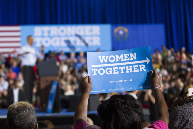 A woman holds up a sign during a speech by President Barack Obama in a campaign rally for Democratic presidential nominee Hillary Clinton at Cheyenne High School on Sunday, Oct. 23, 2016, in North ...
