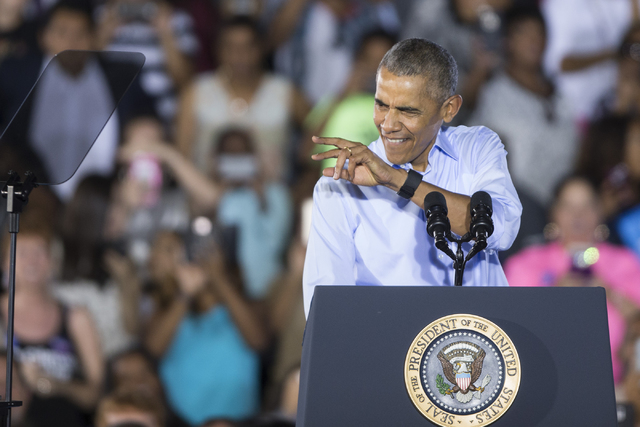 President Barack Obama gestures at supporters during his campaign rally speech for Democratic presidential nominee Hillary Clinton at Cheyenne High School on Sunday, Oct. 23, 2016, in North Las Ve ...