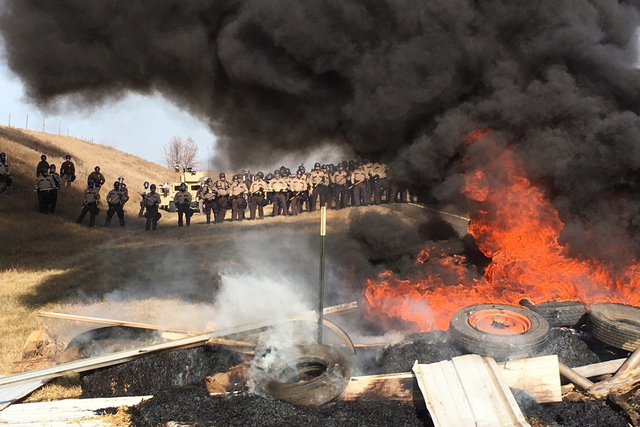 Tires burn as armed soldiers and law enforcement officers stand in formation on Thursday, Oct. 27, 2016, to force Dakota Access pipeline protesters off private land where they had camped to block  ...