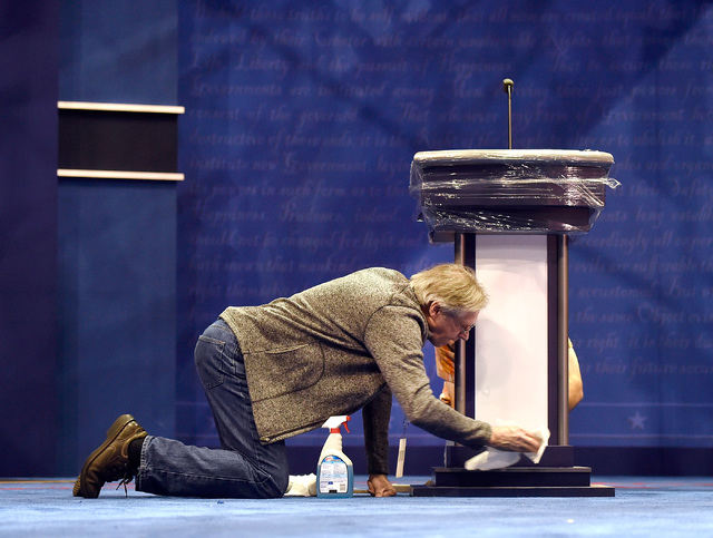 Michael Foley cleans one of the podiums on the debate set at the Thomas & Mack Center at UNLV Monday, Oct. 17, 2016, in Las Vegas. The third and final presidential debate is scheduled for Wedn ...