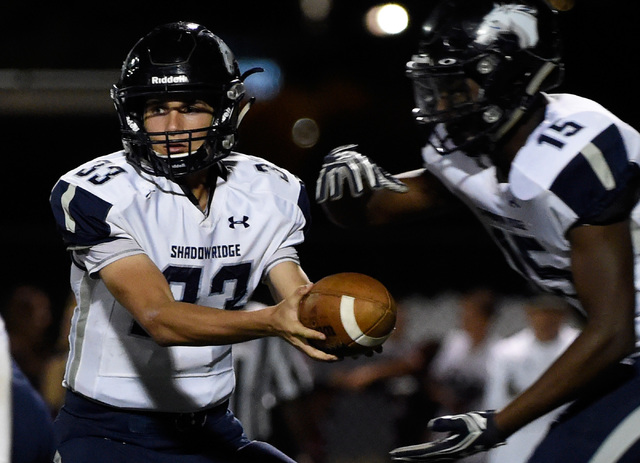 Shadow Ridge quarterback Kody Presser (33) hands the ball off to running back Malik Lindsey during a high school football game against Faith Lutheran at Faith Lutheran High School, Friday, Oct. 21 ...
