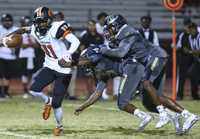 Chaparral's Kentrell Petite (11) runs the ball as Cheyenne's Deriontae Green (5) and William Federson (7) attempt to tackle during a football game at Cheyenne High School in Las Vegas on Thursday, ...