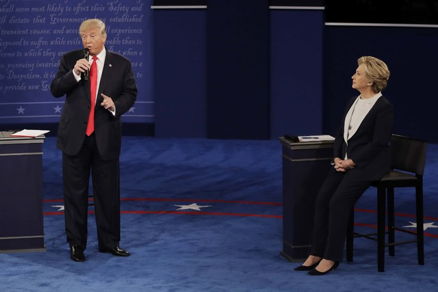 Democratic presidential nominee Hillary Clinton listens to Republican presidential nominee Donald Trump during the second presidential debate at Washington University in St. Louis, Sunday, Oct. 9, ...