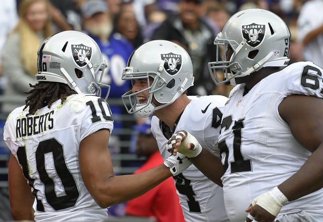 Oakland Raiders wide receiver Seth Roberts, left, celebrates his touchdown with quarterback Derek Carr, center, and center Rodney Hudson in the first half of an NFL football game against the Balti ...