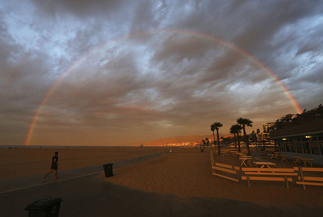A rainbow appears over the beach and ocean shortly after dawn in Santa Monica, Calif., as one of a series of storms sweeps through California Friday, Oct. 28, 2016. (Reed Saxon/The Associated Press)
