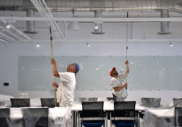 Workers paint as the University of Phoenix's new RedFlint experience center gets ready for it grand opening Monday, Oct. 10, 2016, in downtown Las Vegas. The 11,000 square-foot education campus wi ...