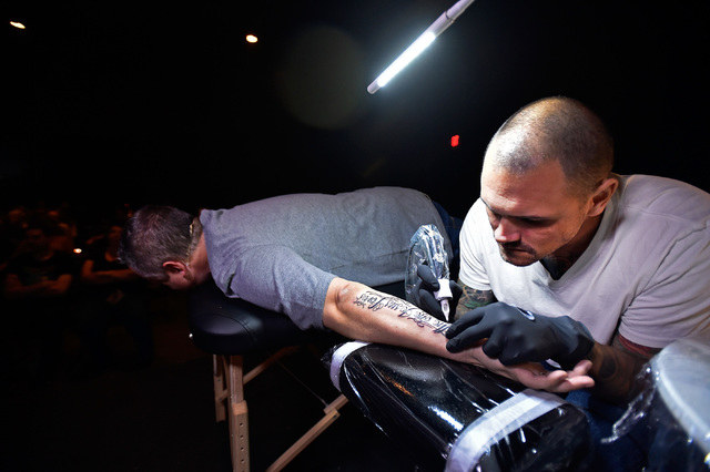 "Tattoo artist Tommy Altman puts the final touches on pastor Vince Antonucci's tattoo during the evening service at Verve Church on Monday, Oct. 3, 2016, in Las Vegas. The tattoo reads ""The one Jes ..."